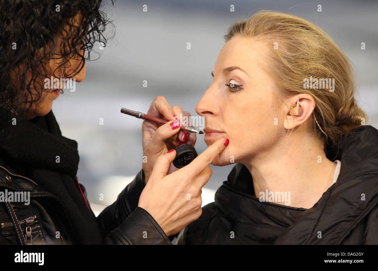 A make-up artist paints the lips of German speed skater Anni