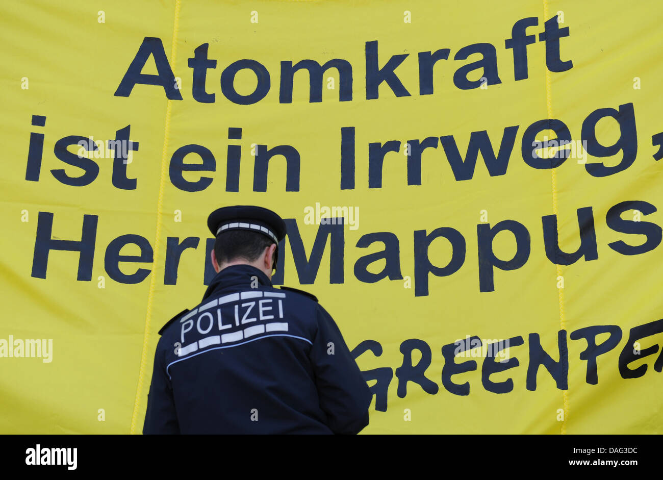 A police officer stands in front of a banner held by Greenpeace activists with the caption 'Nuclear energy is - Stock Image