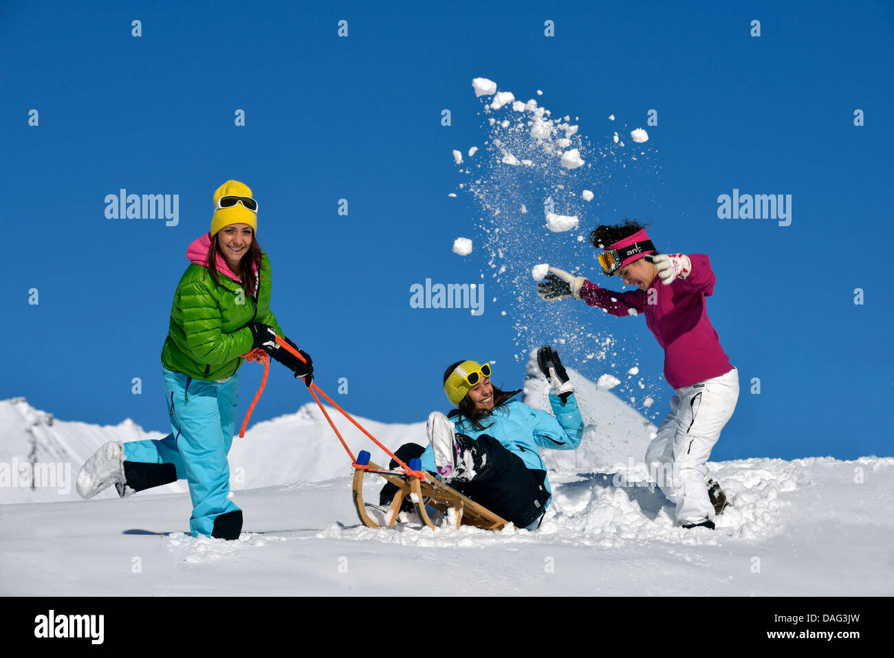 three teenage girls with a sledge fooling around in the snow, France - Stock Image