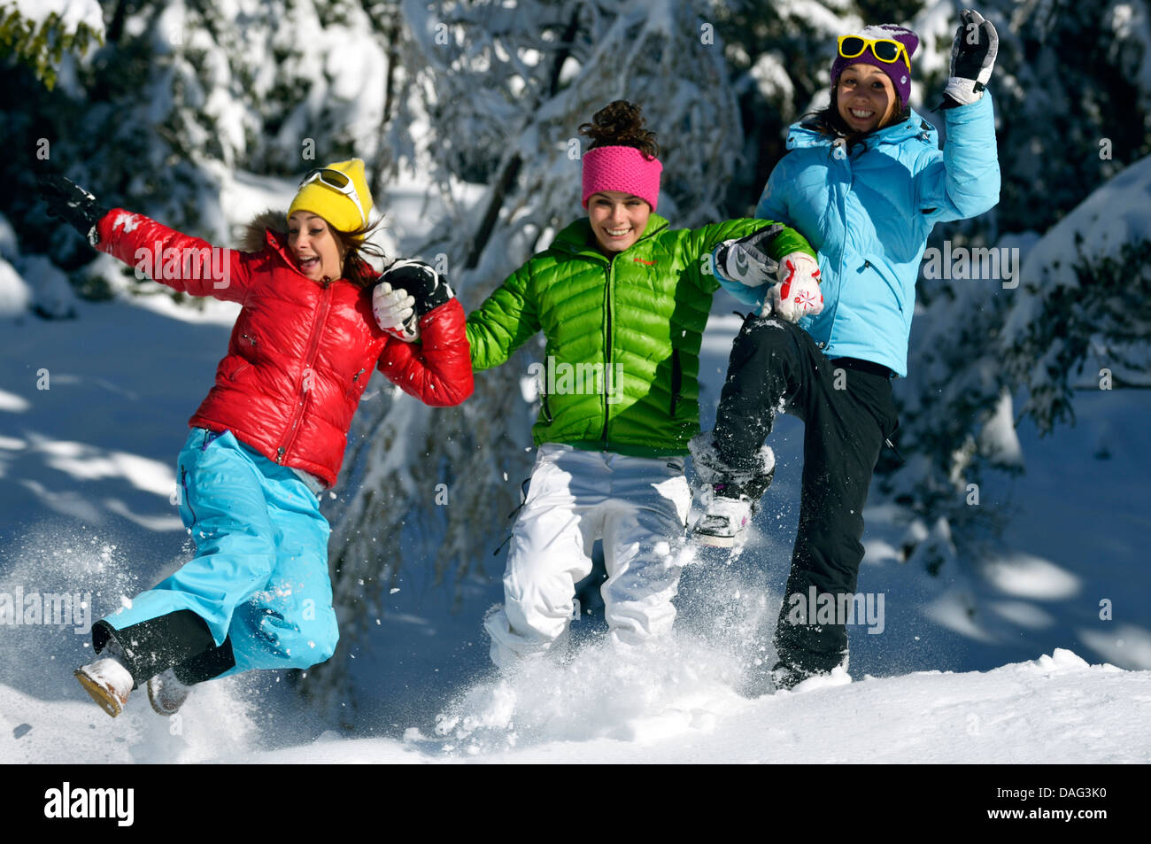three teenage girls frolicly running through a snowbound winter forest, France - Stock Image