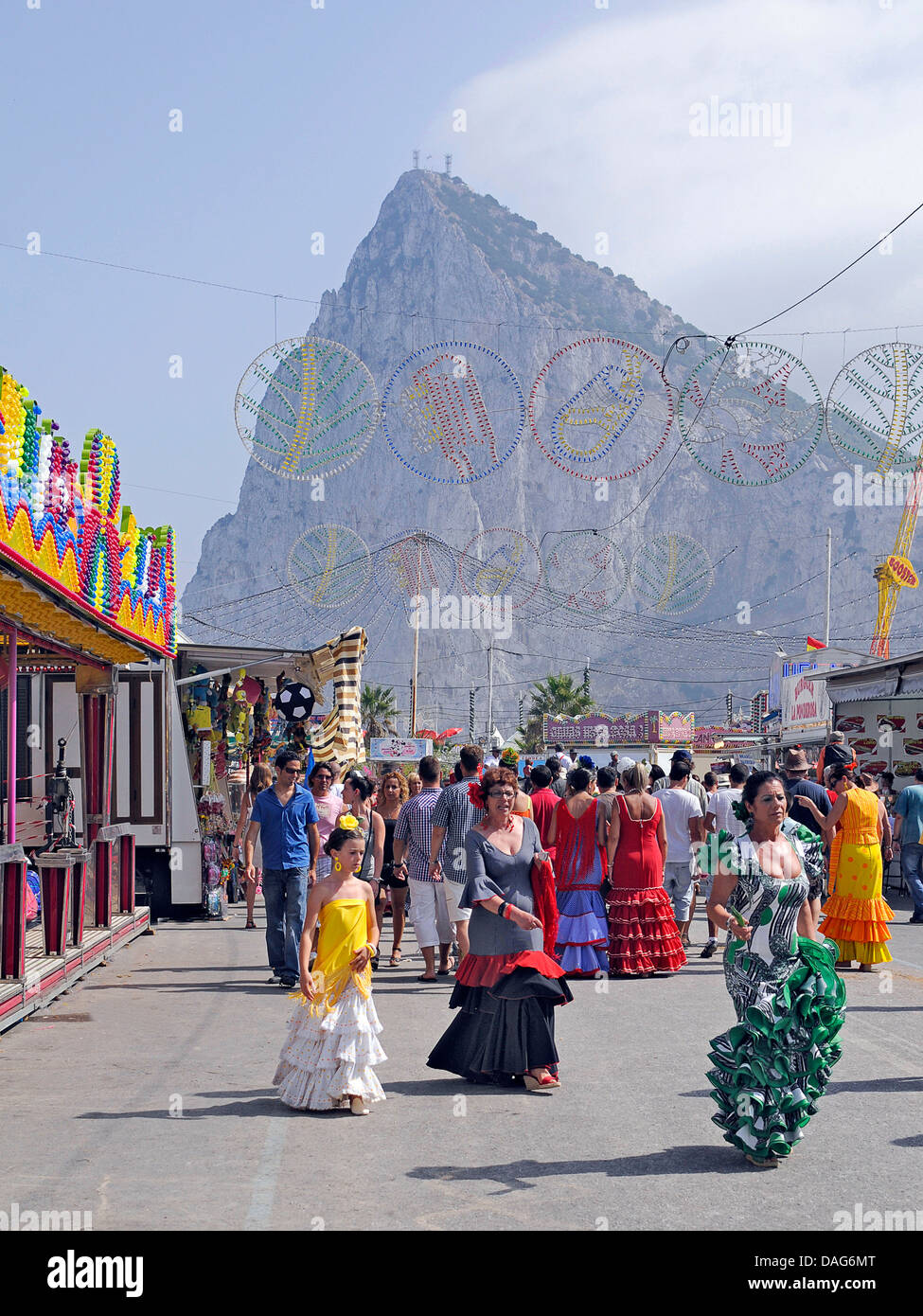 female flamenco dancers celebrating the annual fair, Rock of Gibraltar in background, Spain, La Linea De La Concepcion - Stock Image