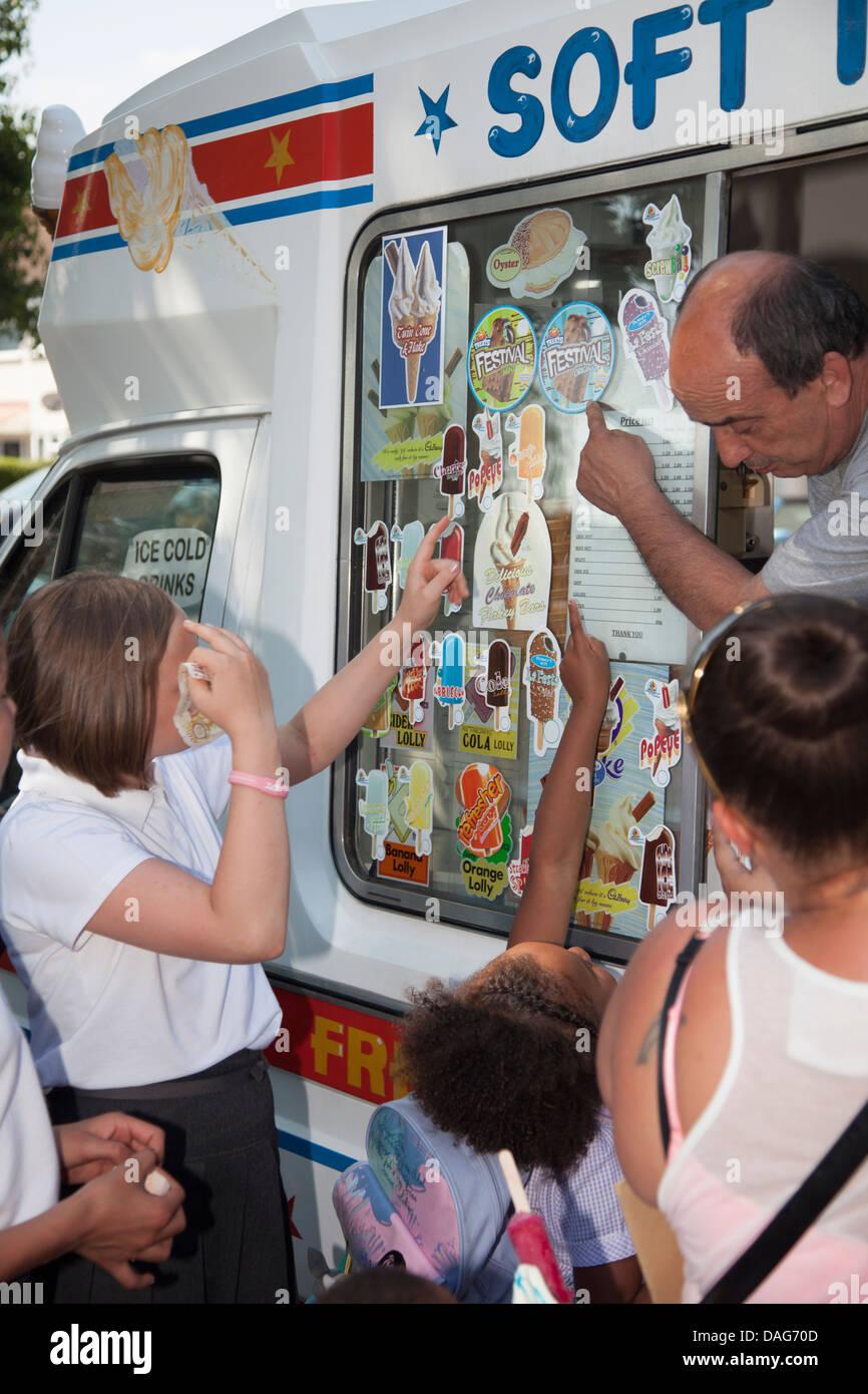 School children buying ice-cream after school from ice-cream van - Stock Image
