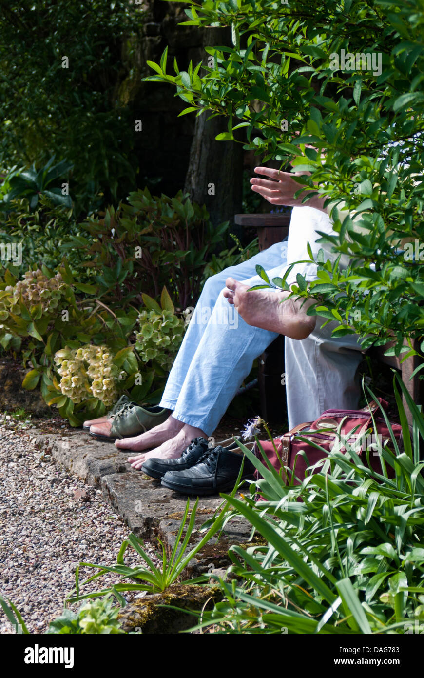 A couple sit and rest their tired feet - Stock Image