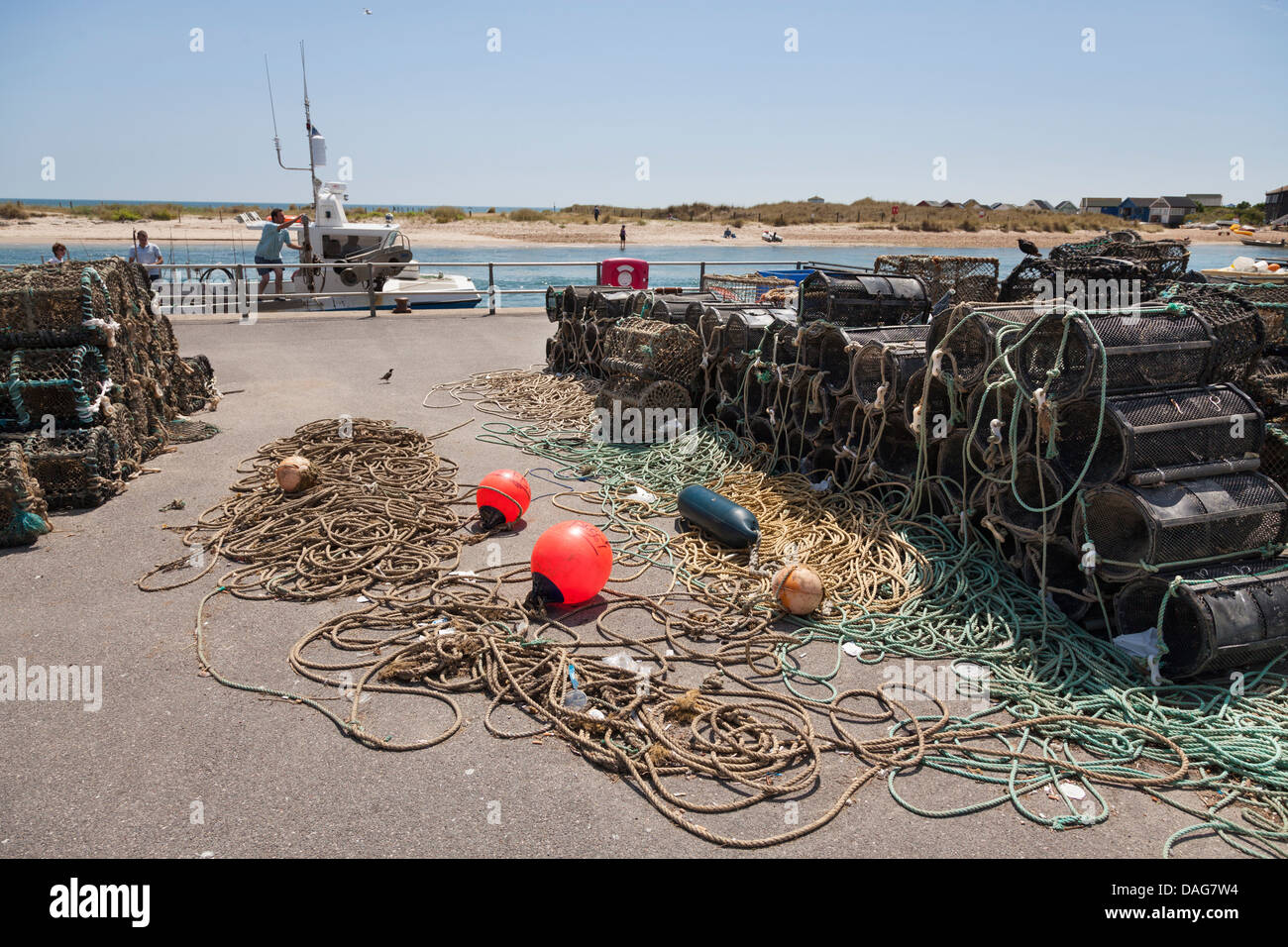 crab and lobster pots and ropes drying in the sun on the quayside - Stock Image