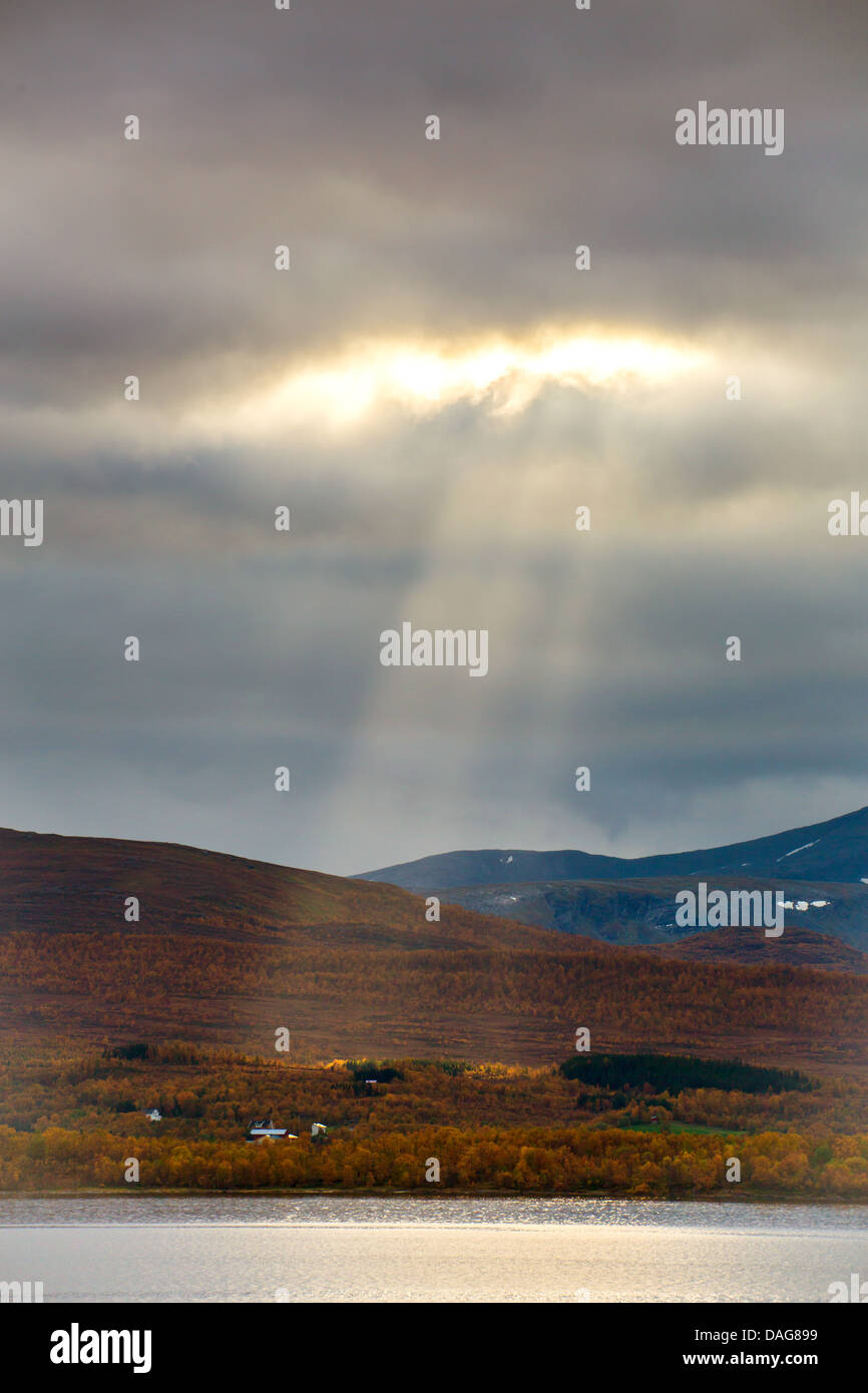 crepuscular rays breaking through the cloud cover over Kvaloeya , Norway, Troms, Tromsoe - Stock Image