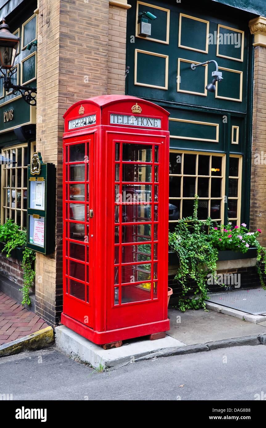 red telephone booth next to a pub - Stock Image