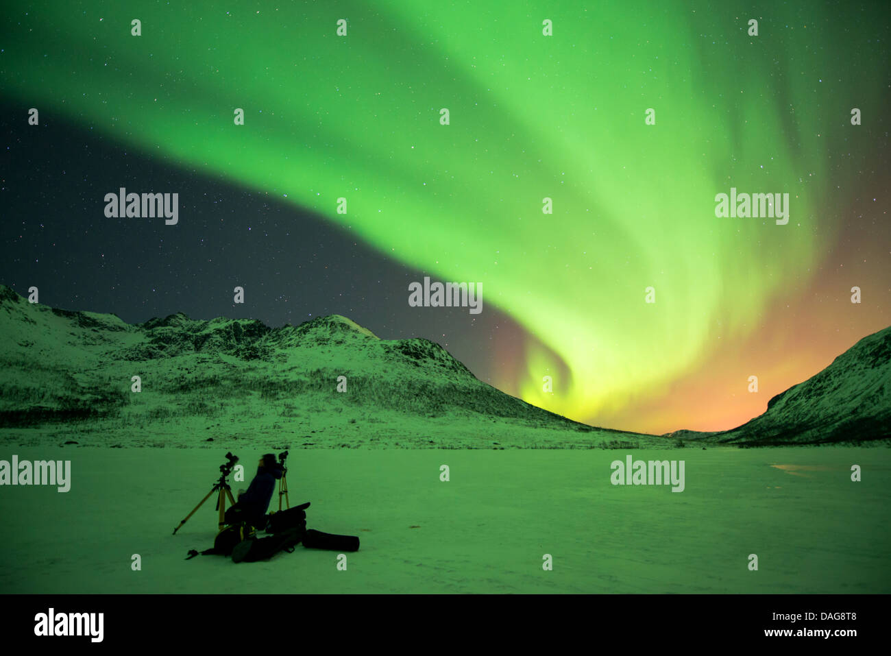 aurora curtain in front of the starry sky over snow-covered valley with a nature photographer's equipment in - Stock Image