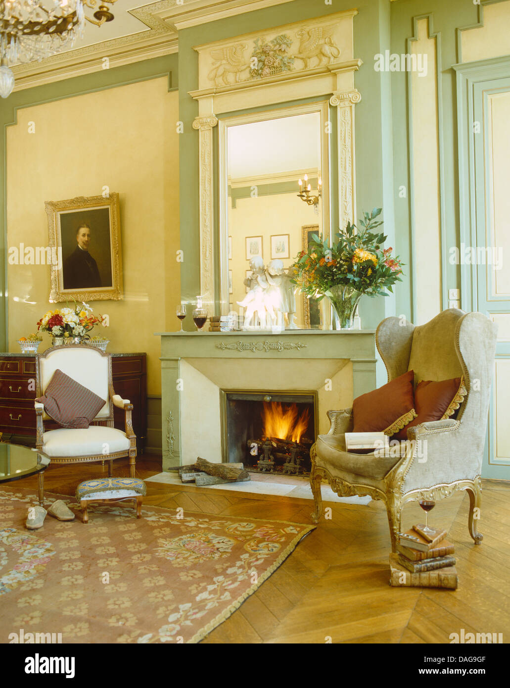 Wing Chair And Small Upholstered Chair On Either Side Of Fireplace Below  Tall Mirror In French Country Sitting Room