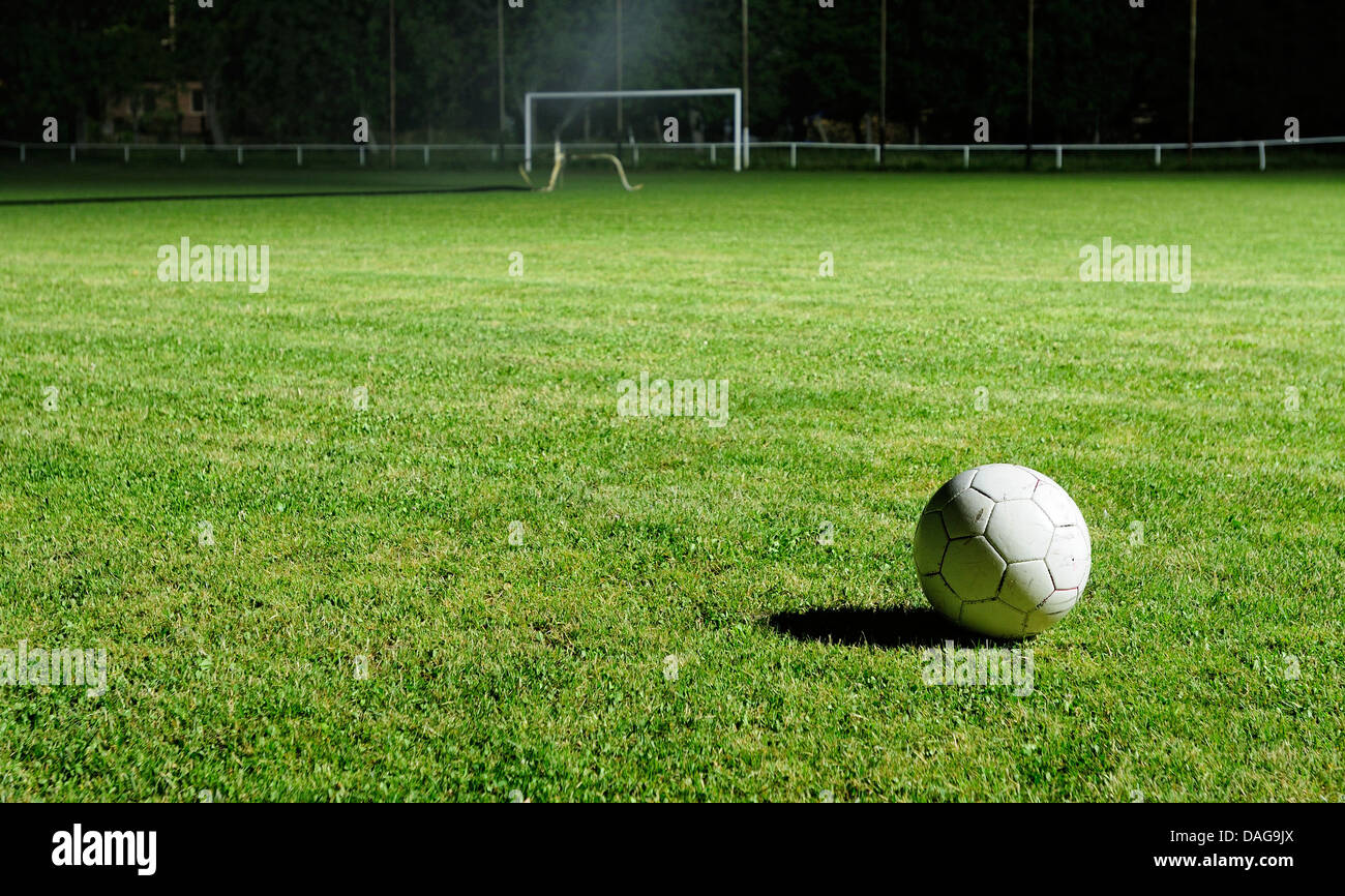 Football pitch at night, with some artificial lightning and a football - Stock Image