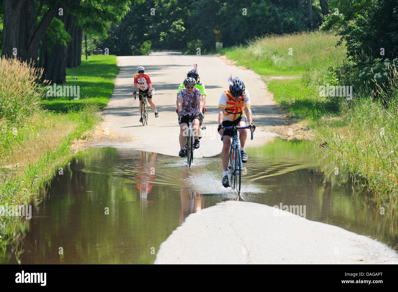 Bicyclists traveling on partially flooded country road. - Stock Image