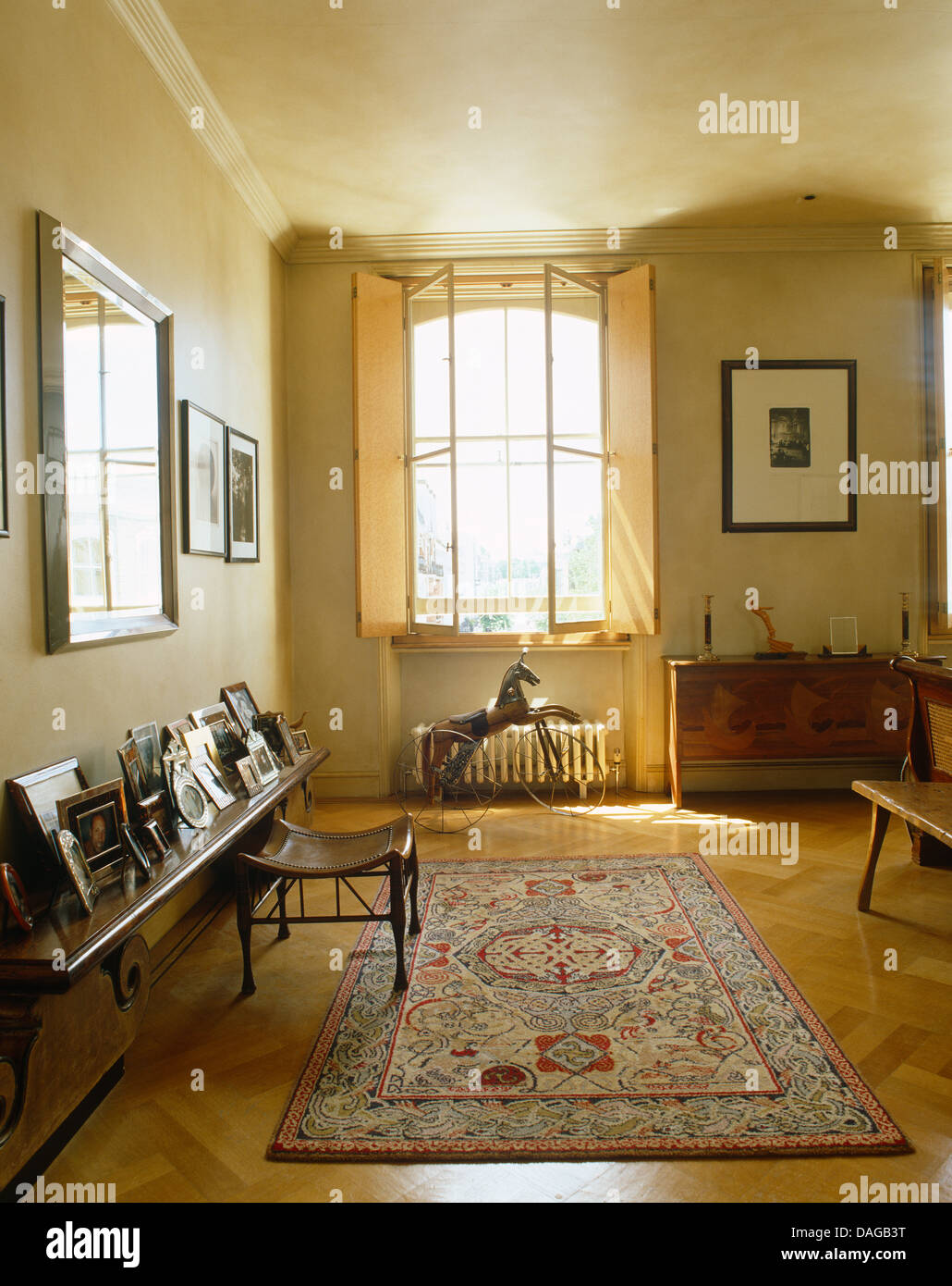 Shutters on window above metal horse in bedroom with patterned rug on parquet floor Stock Photo