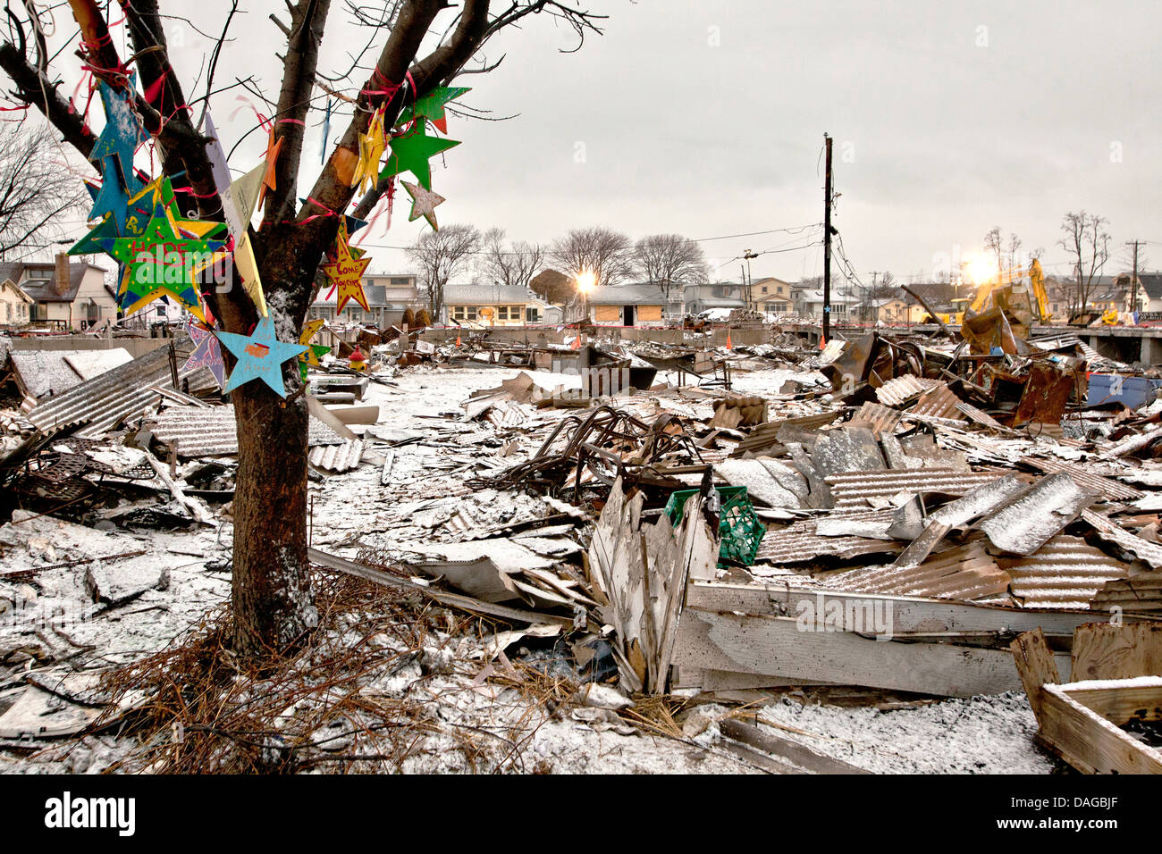 Stars decorate a tree standing amongst homes destroyed by Hurricane Sandy February 8, 2013 in Breezy Point, NY. - Stock Image