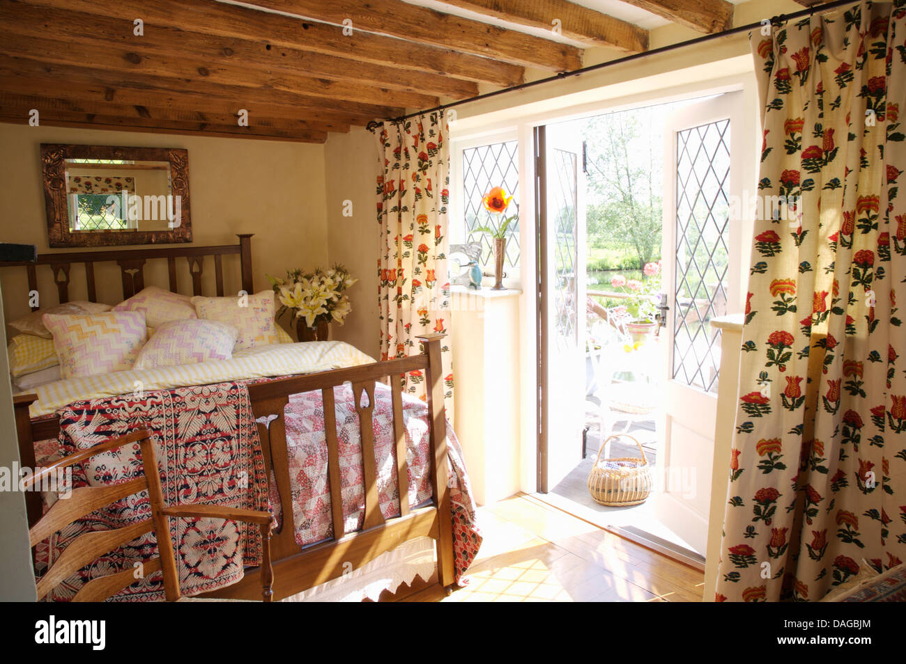 Floral Curtains At French Windows To Balcony In Cottage Bedroom With Pink Quilt On Simple Wooden Bed