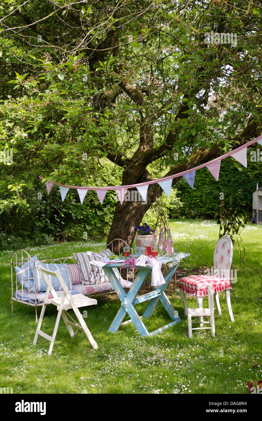 Bunting On Tree Above Lawn With Painted Table And Chairs And Vintage Daybed  In Country Garden In Summer