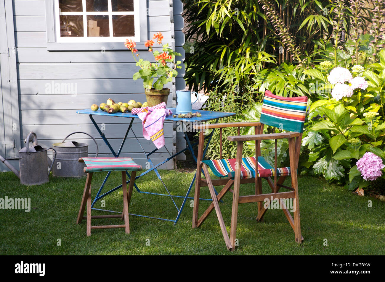 Striped Directoru0027s Chair And Stool Beside Blue Painted Metal Table On Lawn  In Front Of Blue Painted Shed In Country Garden