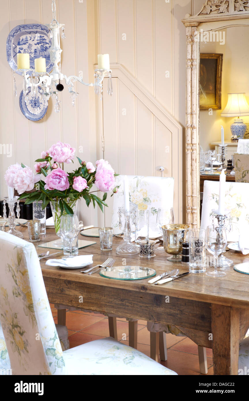 Vase Of Pink Peonies On Table Set For Dinner In Country Dining Room With  Large Mirror And Painted Tongue+groove Paneled Walls