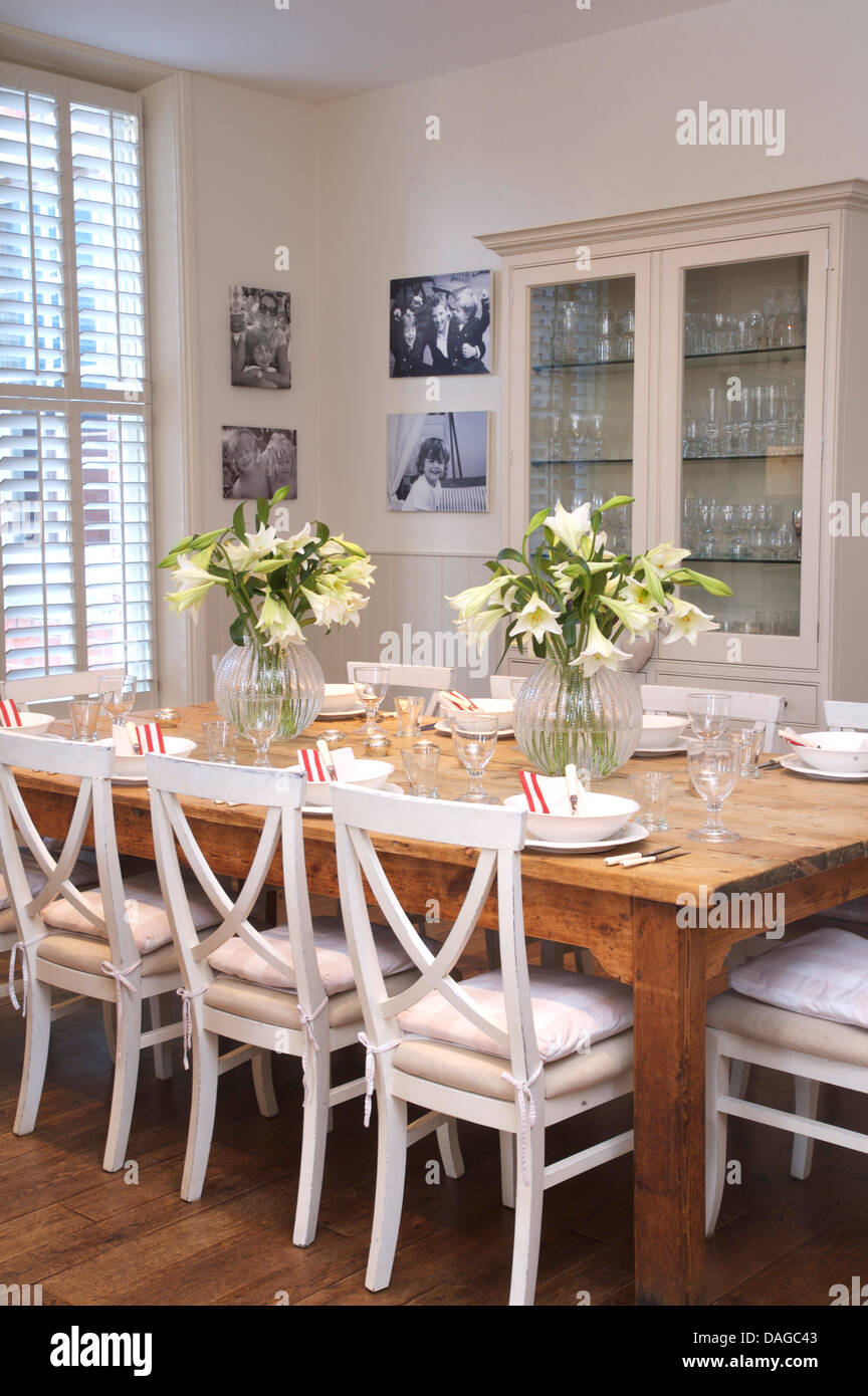 White Painted Chairs At Plain Wood Table In Country Dining Room With White  Glass Front Cupboard And Plantation Shutters