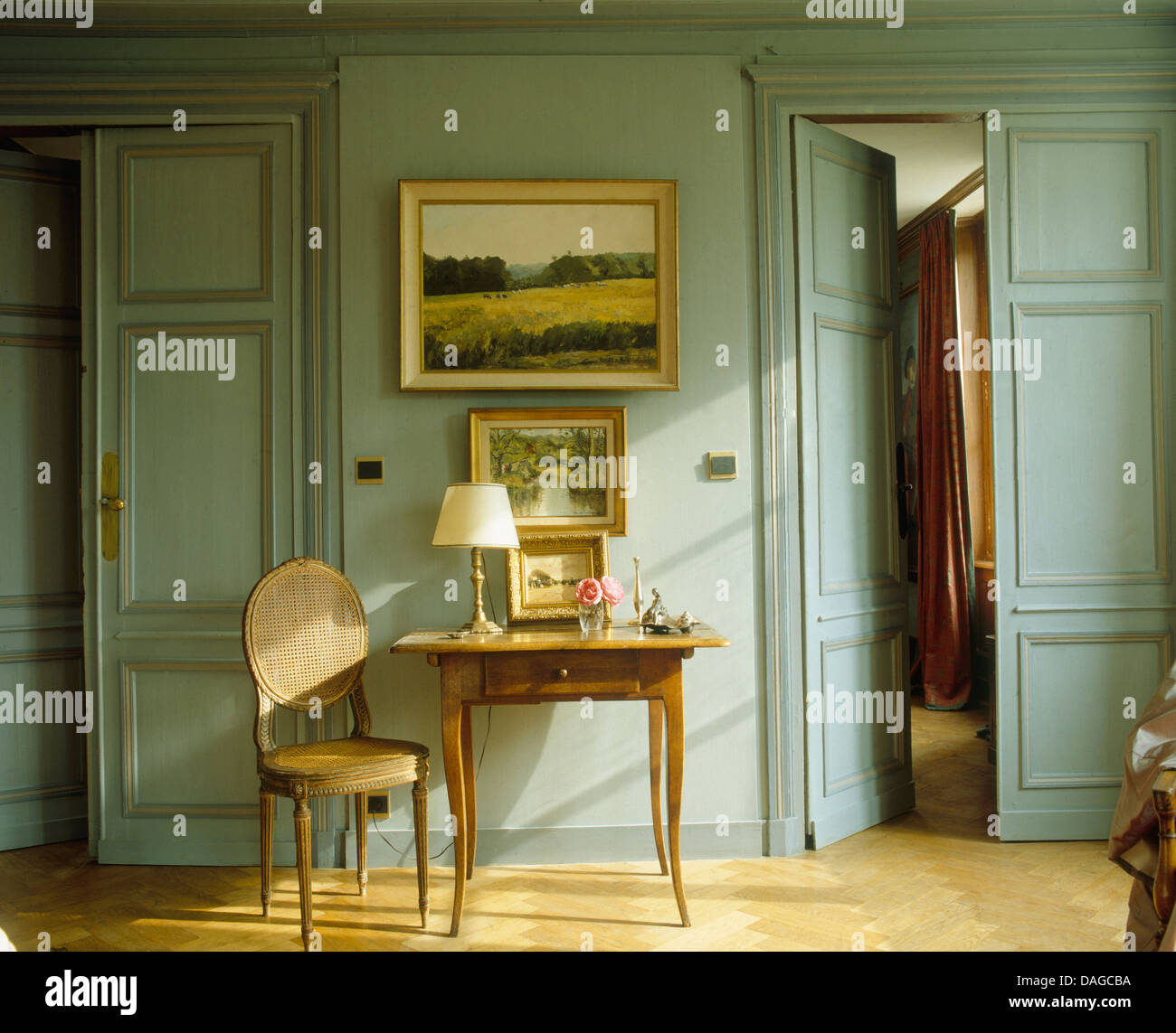 Landscape painting on wall above small antique table and chair and pale  gray paneled French hall with half open double doors - Landscape Painting On Wall Above Small Antique Table And Chair And