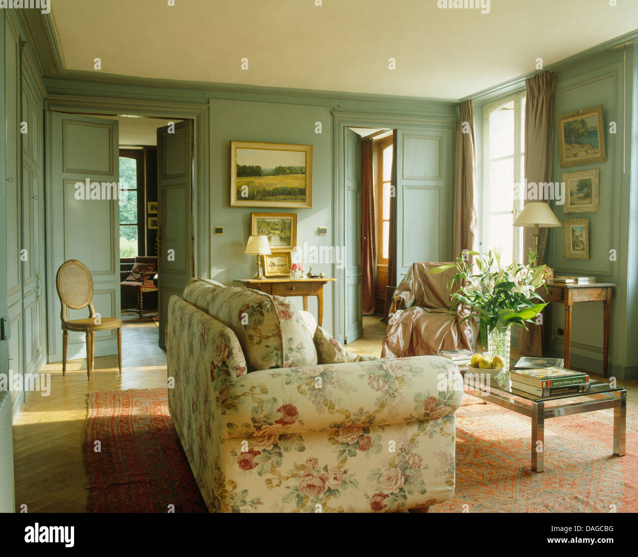 Floral sofa in French country living room with gray-green painted ...