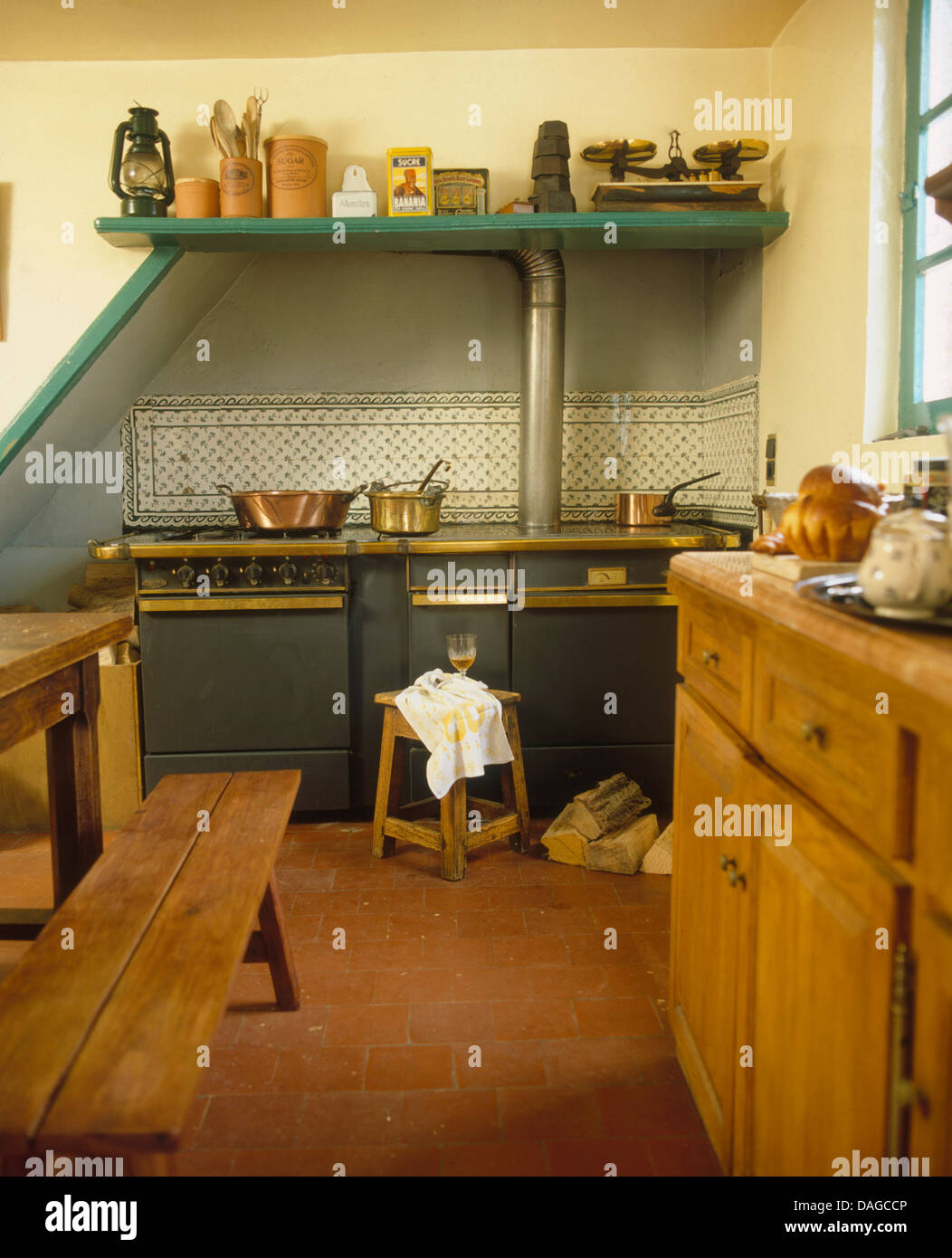 Range Oven And Quarry Tiled Floor In French Country Kitchen With Rustic Wooden  Bench And Table