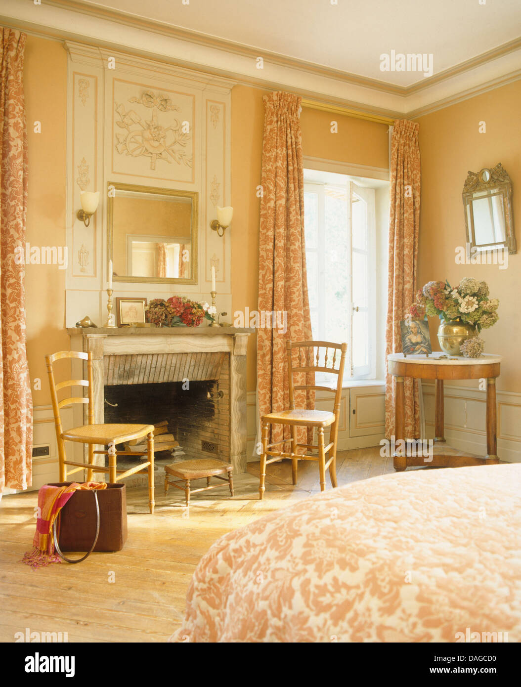 Antique Chairs On Either Side Of Fireplace In Bedroom Of French Chateau  With Vase Of Flowers On Small Table Beside Window