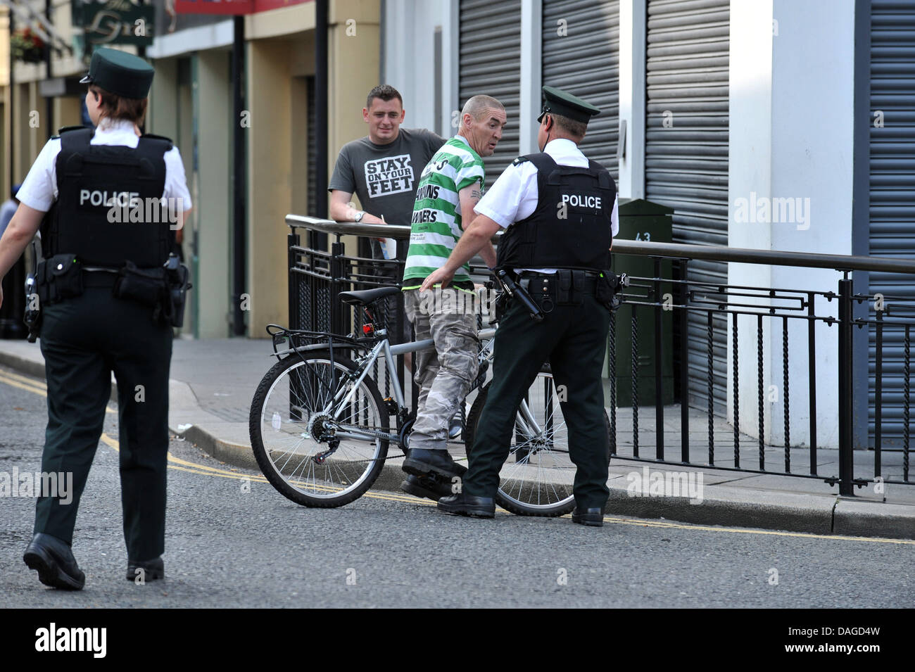 Londonderry, Northern Ireland, UK. 12th July 2013. PSNI officers stop a nationalist close to where  local  members - Stock Image