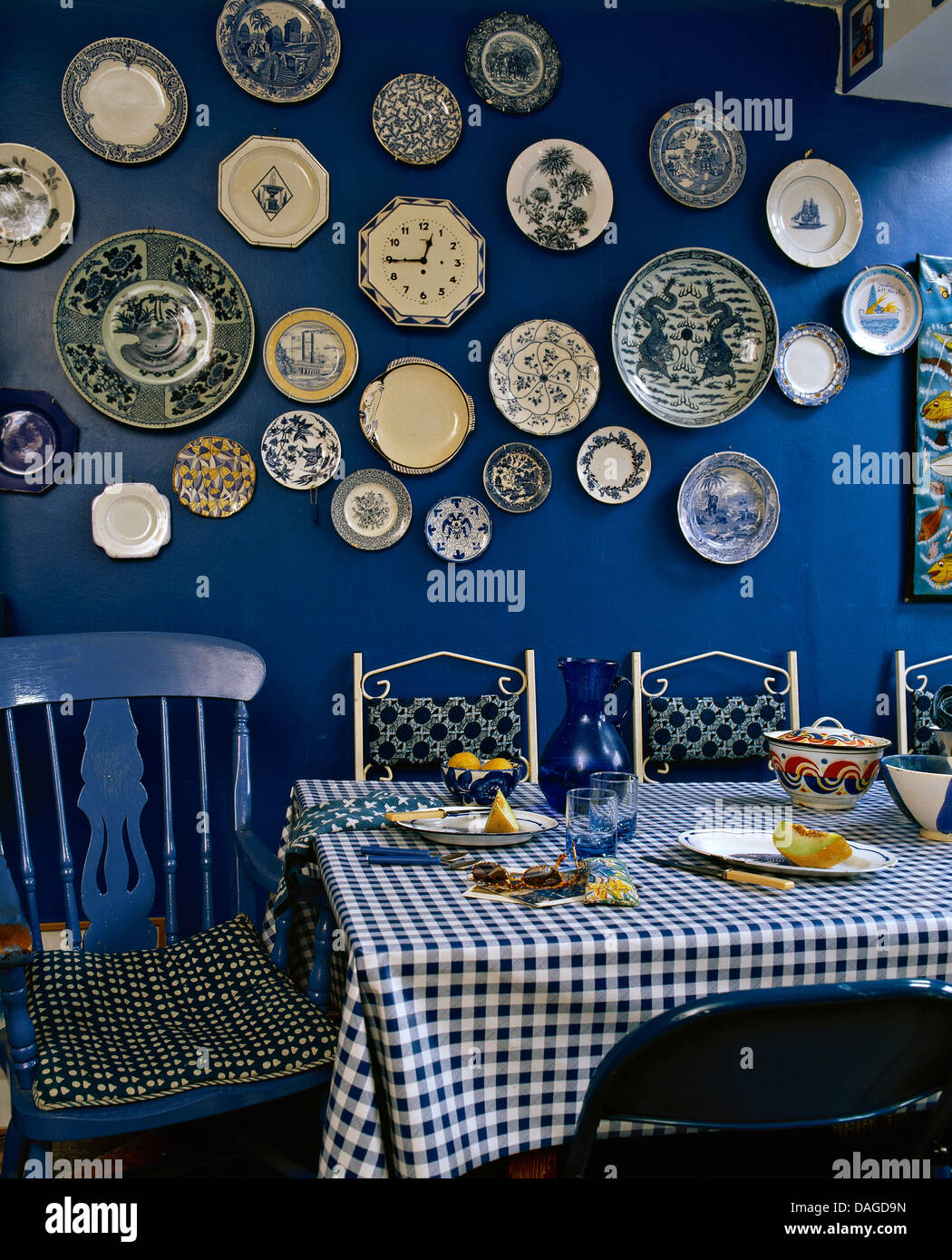 Collection of pottery plates on wall of deep blue dining room with blue chair at table with blue checked PVC cloth & Collection of pottery plates on wall of deep blue dining room with ...