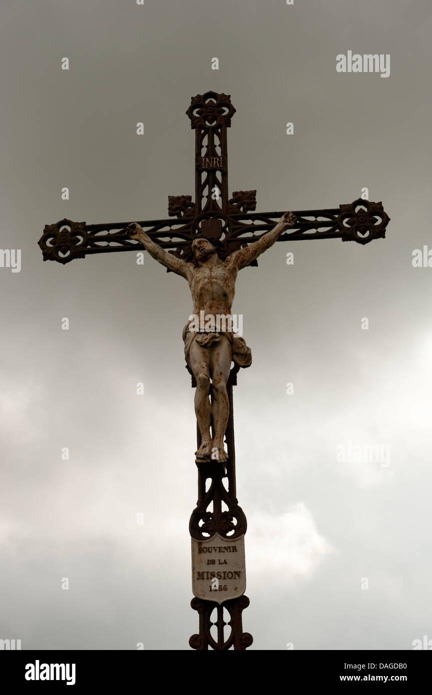 Christ Crucifix dark foreboding grey sky Bonningues-les-Ardres France - Stock Image