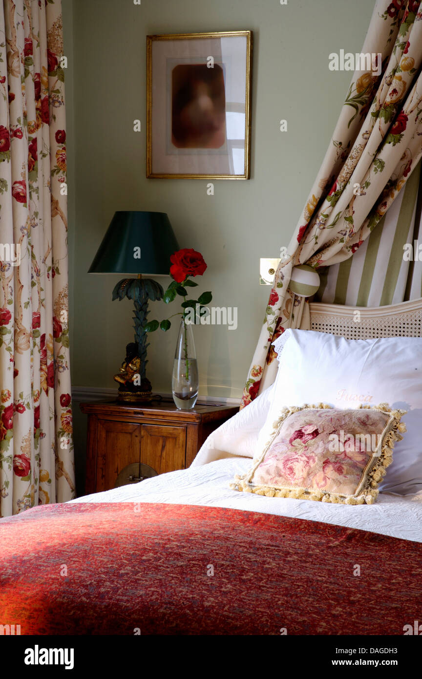 Floral Drapes Above Bed With White Pillows And Red Bed Cover In Pale Green Bedroom With Green Lamp On Bedside Table Stock Photo Alamy