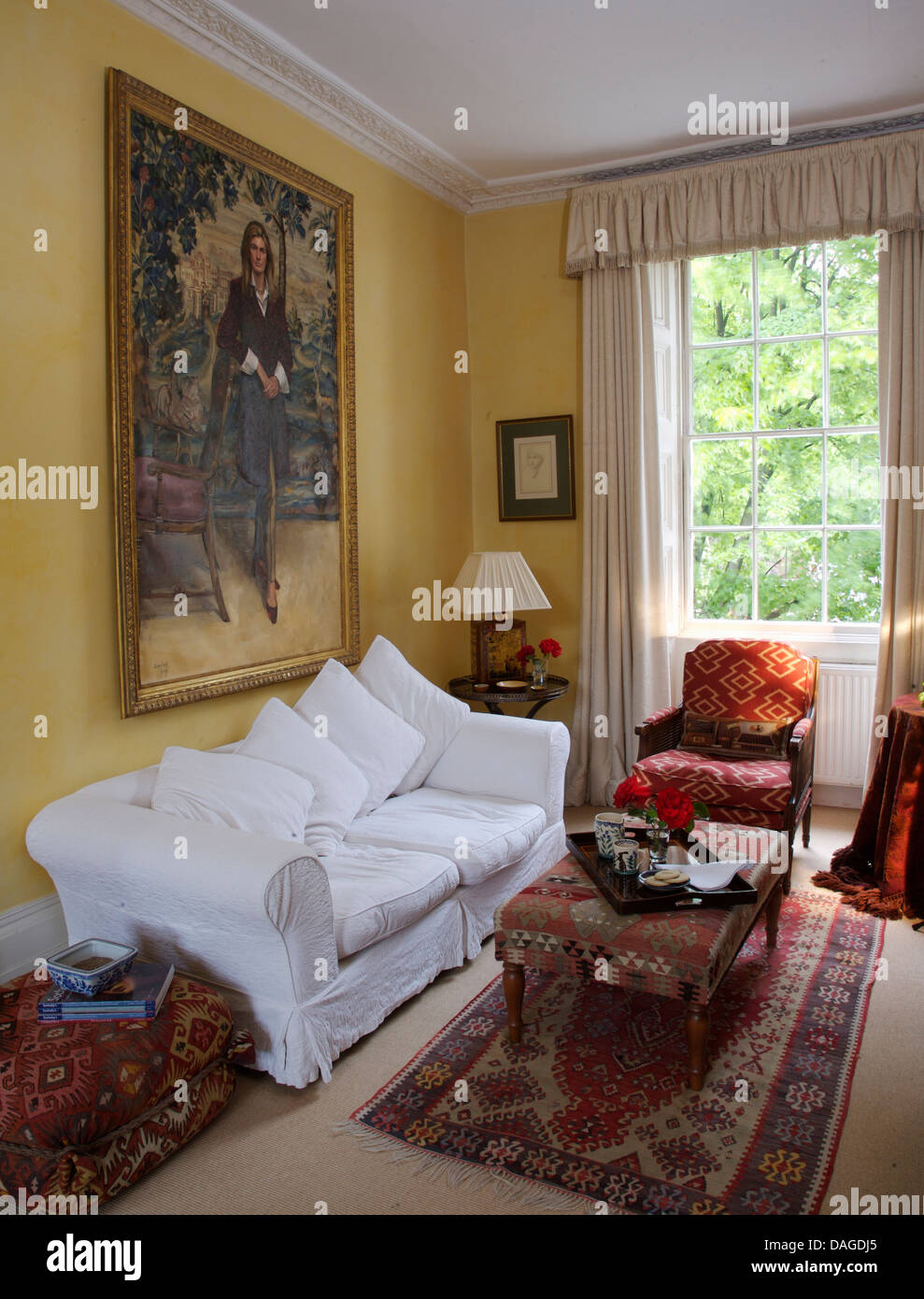 Large Painting Above Sofa With White Loose Cover In Town House Drawing Room  With Kelim Upholstered Stool On Small Rug