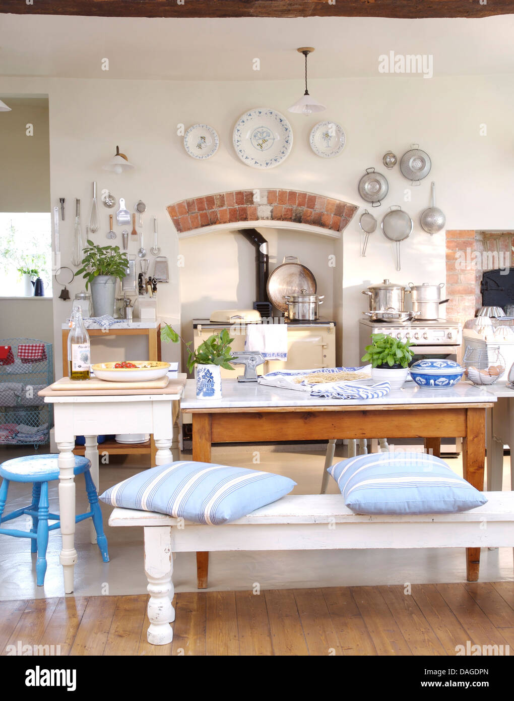 Charming Blue Striped Cushion On White Bench At Simple Wooden Table In Country  Kitchen With Display Of Plates And Pans On Wall Above Aga
