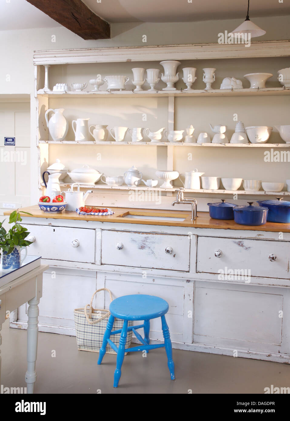 White china displayed on shelves above sink in white built in dresser in cottage kitchen with bright blue stool