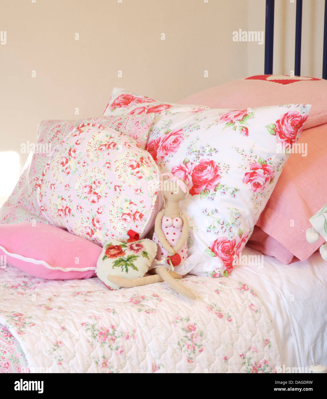Close-up of pink rose patterned cushions on bed with rose ...