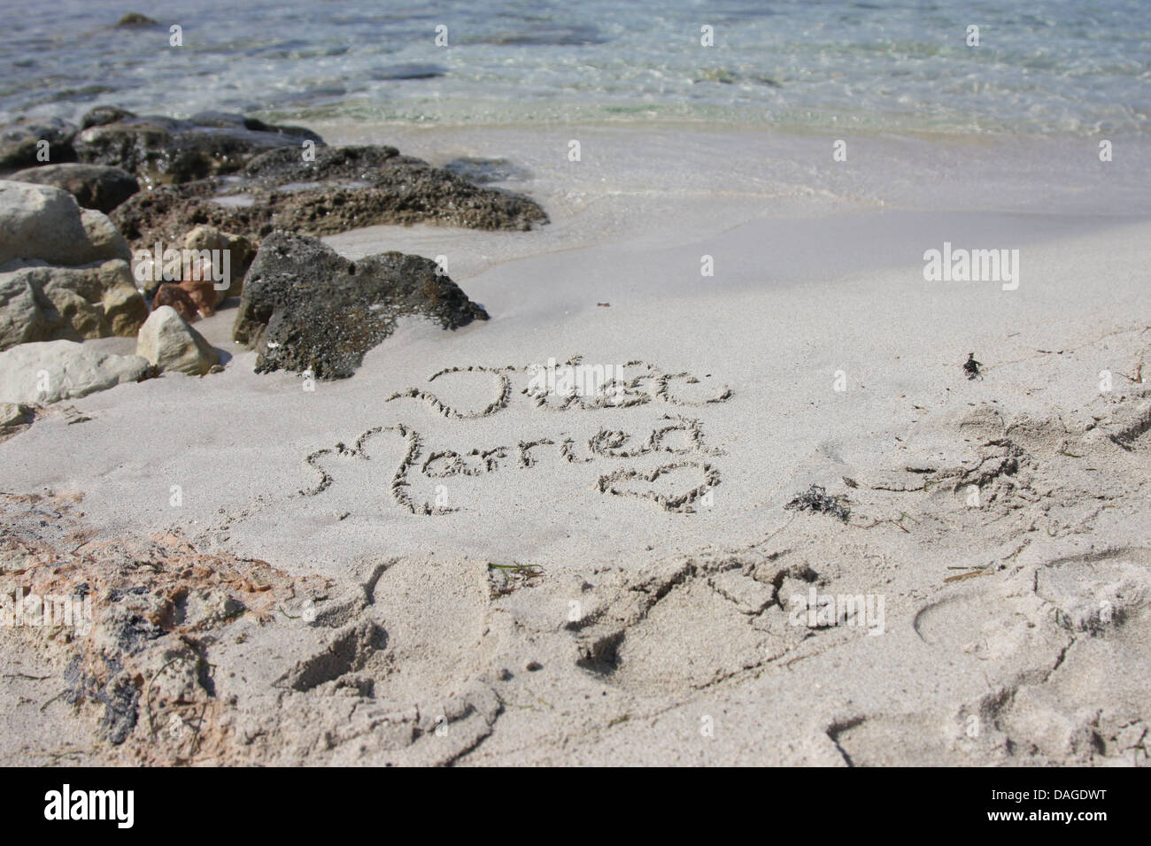 Just married in sand on beach - Stock Image