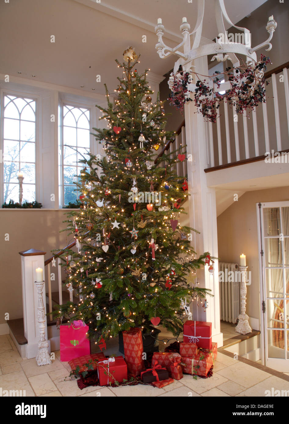 Gift Wrapped Presents In Bright Red Paper Below Tall Decorated Christmas Tree In Country Hall With White Metal Chandelier