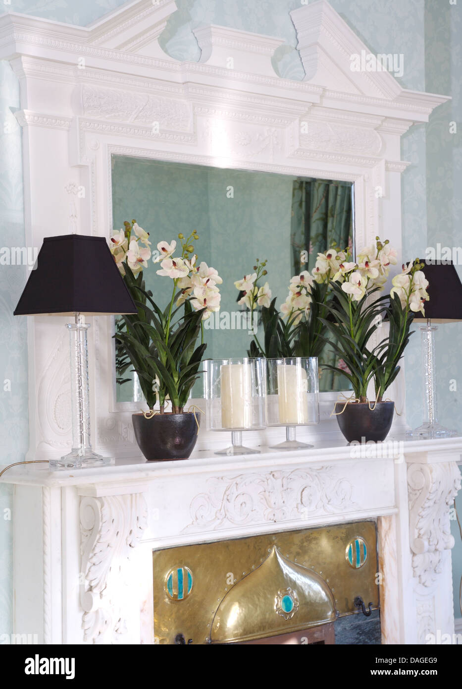 Close Up Of Ornate White Mirror Above Mantelpiece With Black Lamps