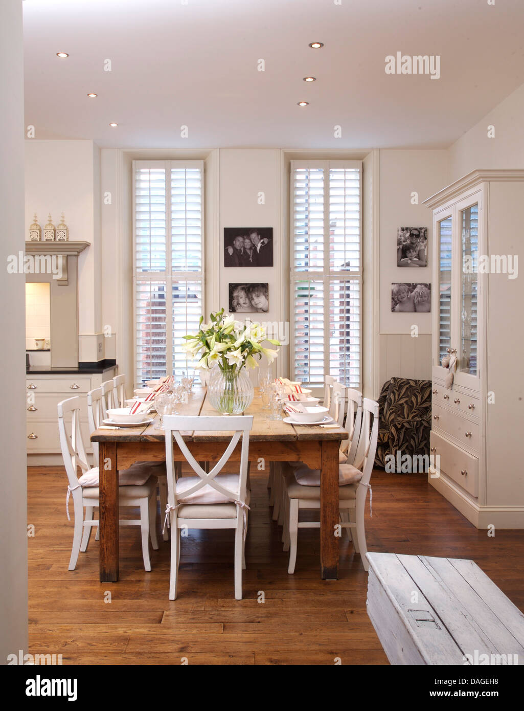 White Chairs At Simple Wood Table In Modern White Kitchen Dining Room With  Wooden Flooring And White Plantation Shutters