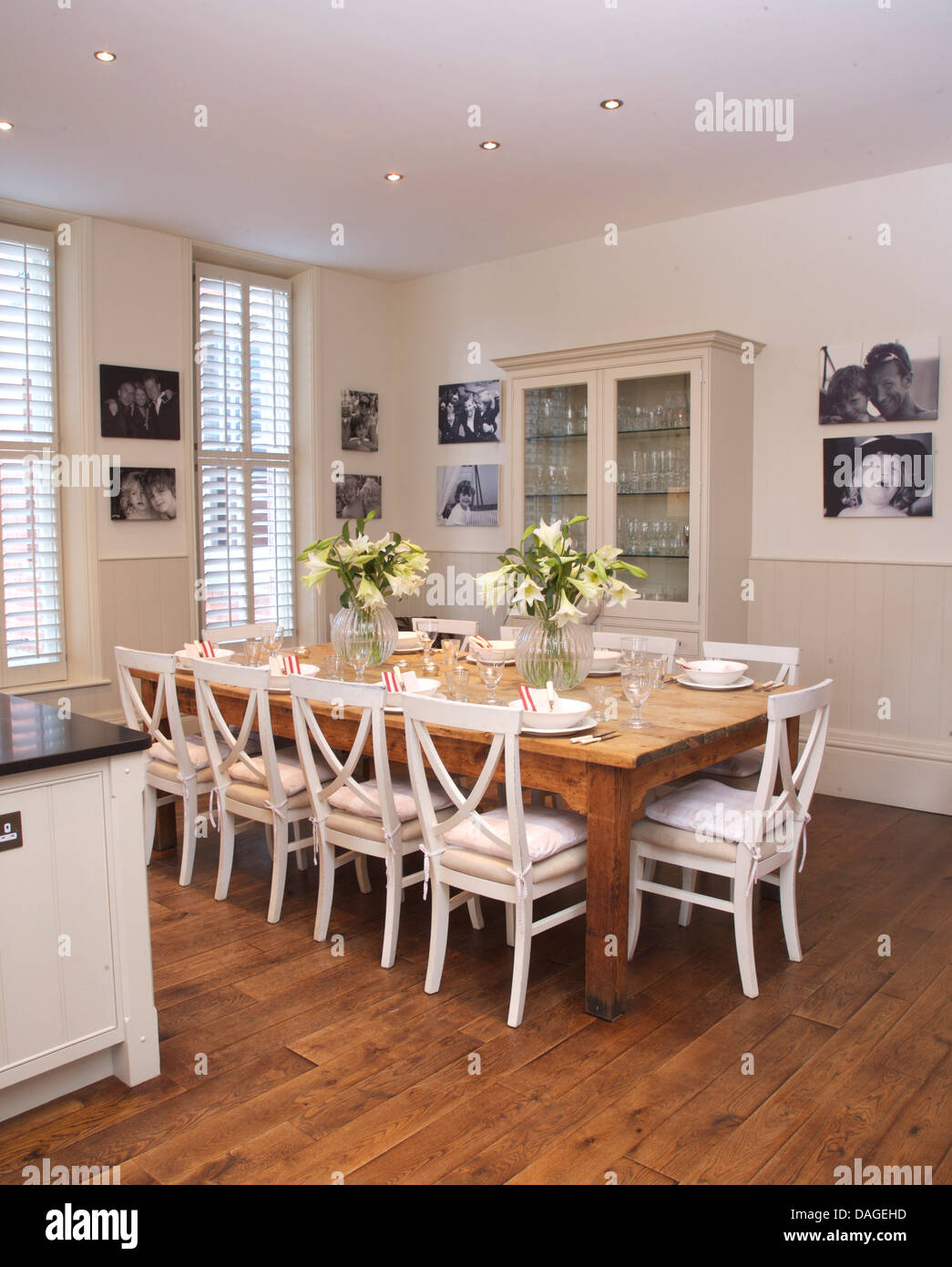 White Chairs At Simple Wood Table In Modern White Kitchen Dining Room With  Wooden Flooring And Framed Black+white Photographs
