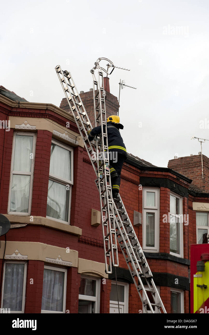 Firefighter Carrying Roof Ladder Up 135 Ladder Uk Stock