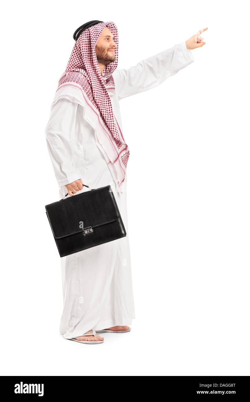 Full length portrait of a male arab person holding a leather suitcase and pointing - Stock Image