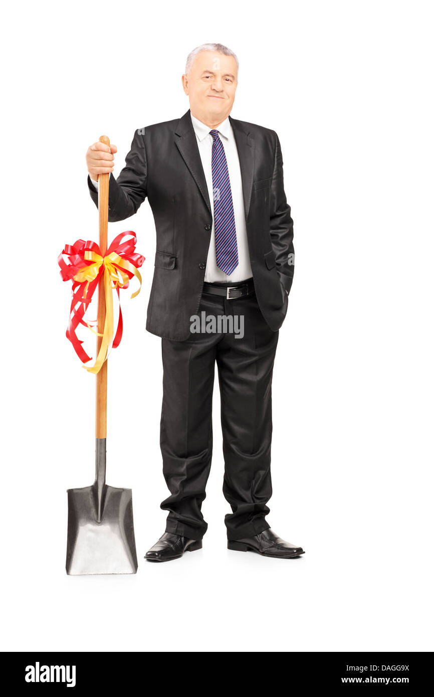 Full length portrait of an investor holding a shovel with ribbon on it and looking at camera - Stock Image