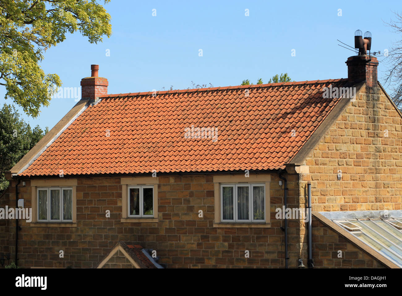exterior of brick house with red roof tiles england stock photo