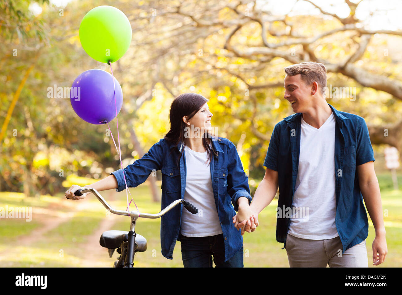 beautiful teenage couple walking in park holding hands - Stock Image
