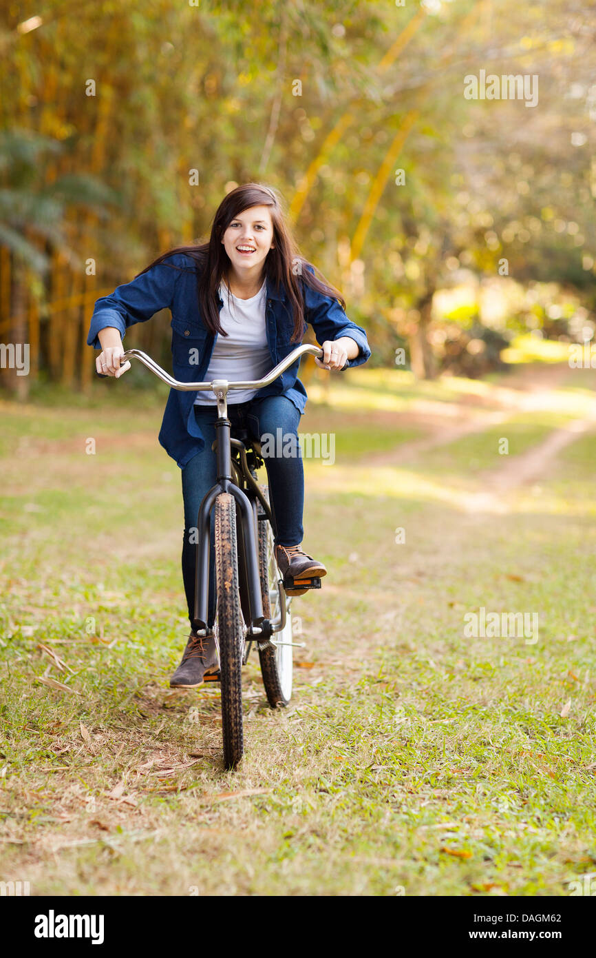 cute teenage girl riding a bicycle outdoors in the park - Stock Image