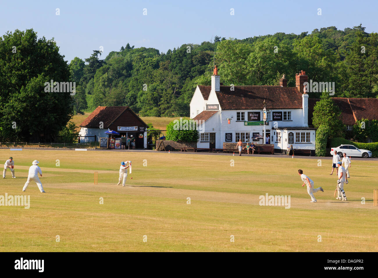 Local teams playing a cricket match on village green with scorched grass in front of Barley Mow pub on a summer - Stock Image