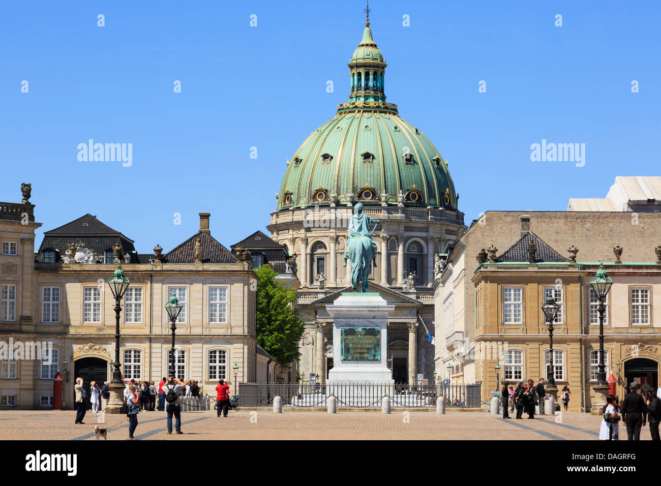 Tourists in Copenhagen's Amalienborg or Royal Palace courtyard with dome of Marble church (Frederik's Church) - Stock Image
