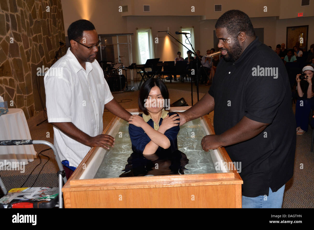 Two black pastors baptize an Asian girl during a church service in Riverdale Park, - Stock Image