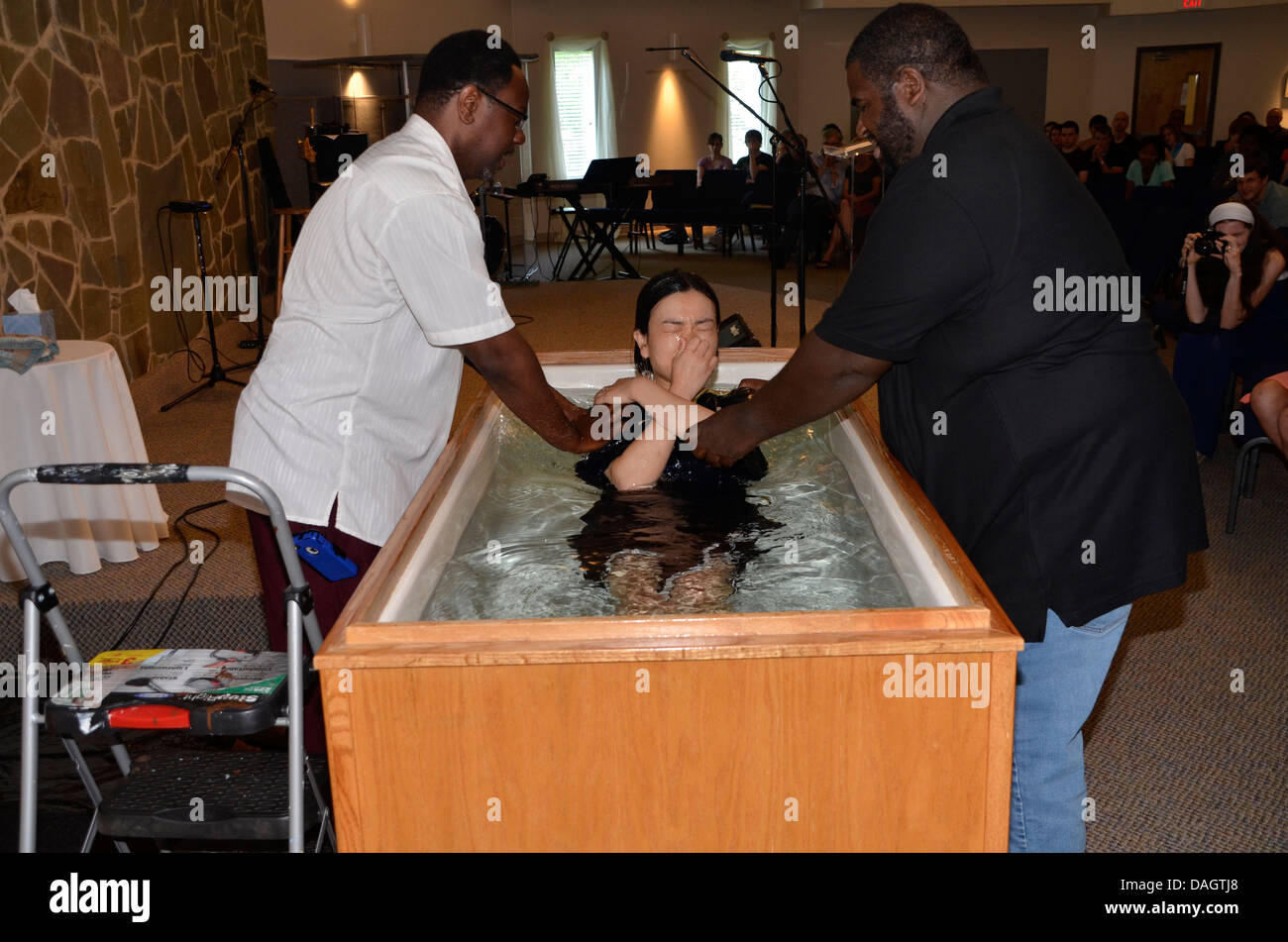 Two black pastors baptize an Asian girl during a church service in Riverdale Park, Maryland - Stock Image