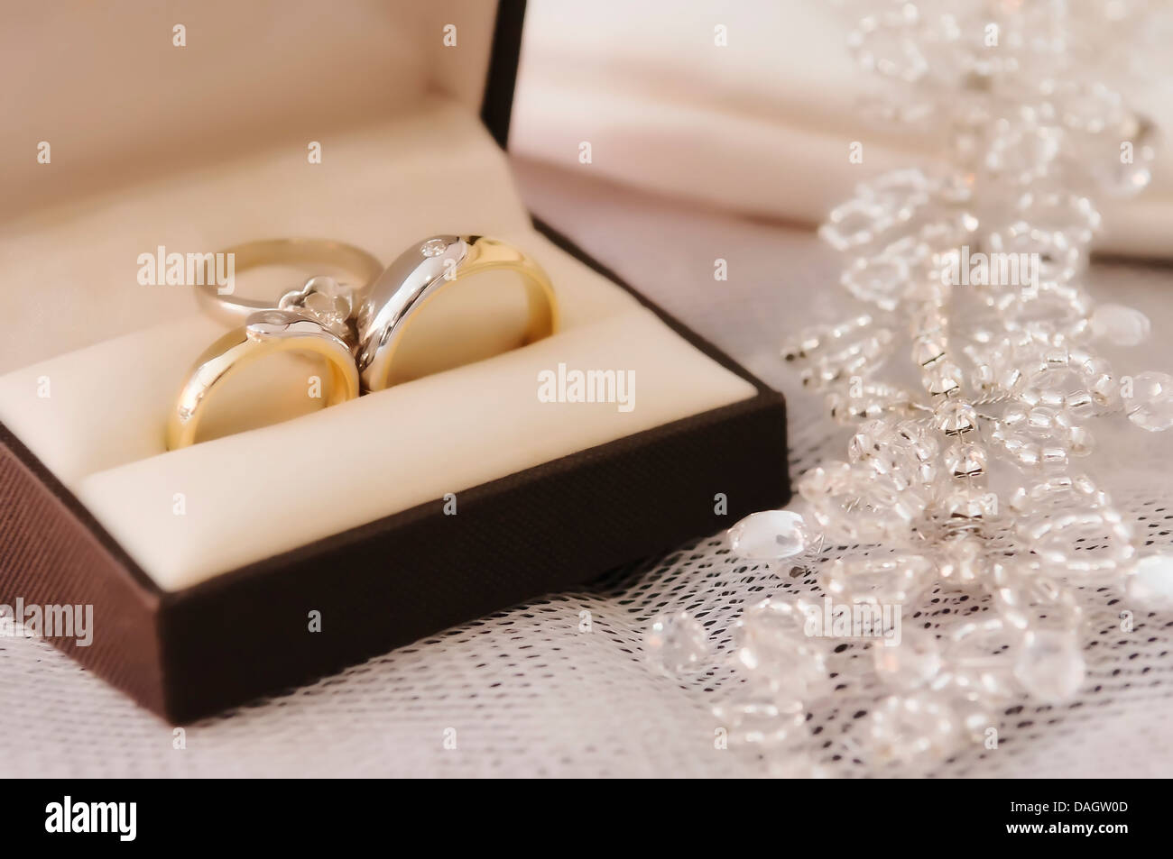 gold wedding rings with engagement ring inside box stock