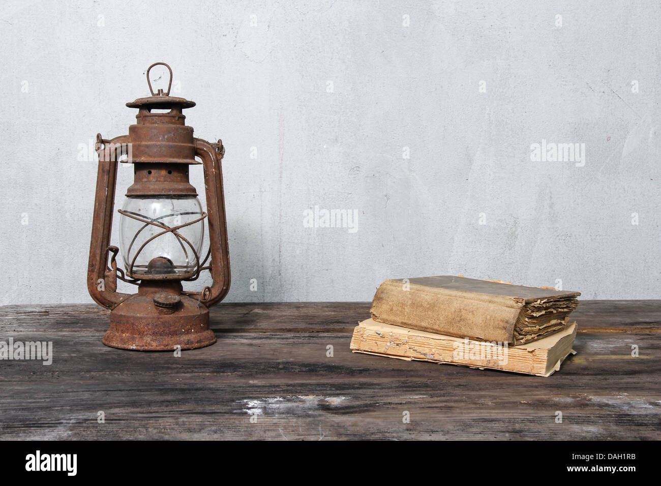 rustic oil lamp on wooden table and old books - Stock Image